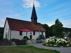 Gartnergepflegtes Grabfeld auf dem Friedhof Aach mit Blick auf die Sankt Remigiuskapelle